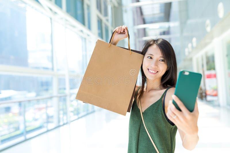 Mulher que guarda o saco de compras e que toma o selfie fotografia de stock