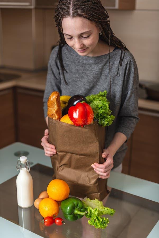 Mulher que guarda o saco de papel completo com os produtos nas mãos no fundo da cozinha Alimento biológico saudável e fresco fotos de stock royalty free