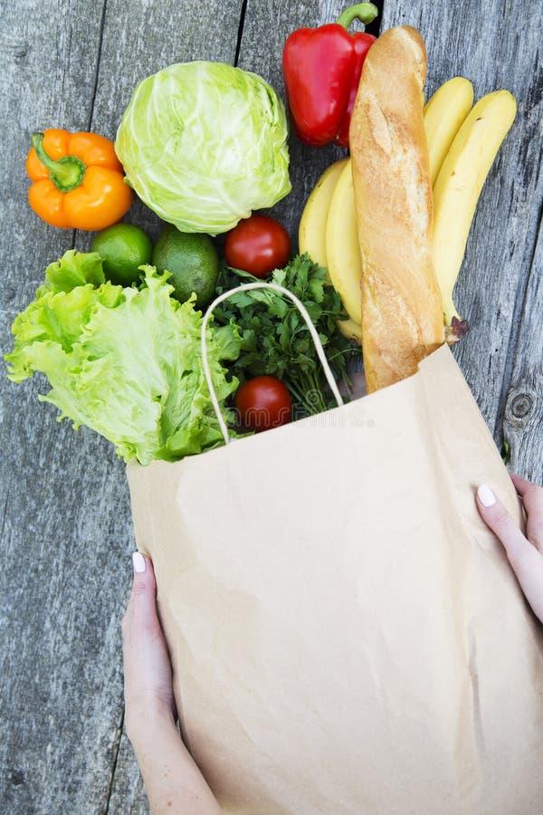Mulher que guarda o saco de papel completo de produtos saudáveis na tabela de madeira De cima de fotos de stock royalty free