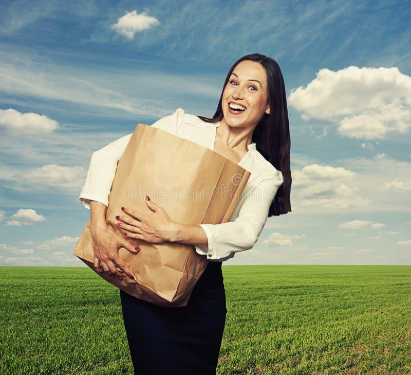 Mulher que guarda o saco de papel pesado em exterior foto de stock royalty free