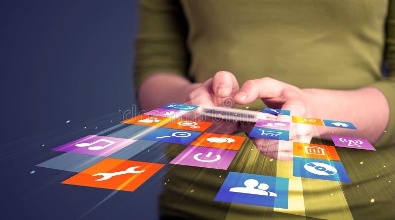 Mulher que guarda o telefone esperto com ícones coloridos da aplicação imagens de stock royalty free