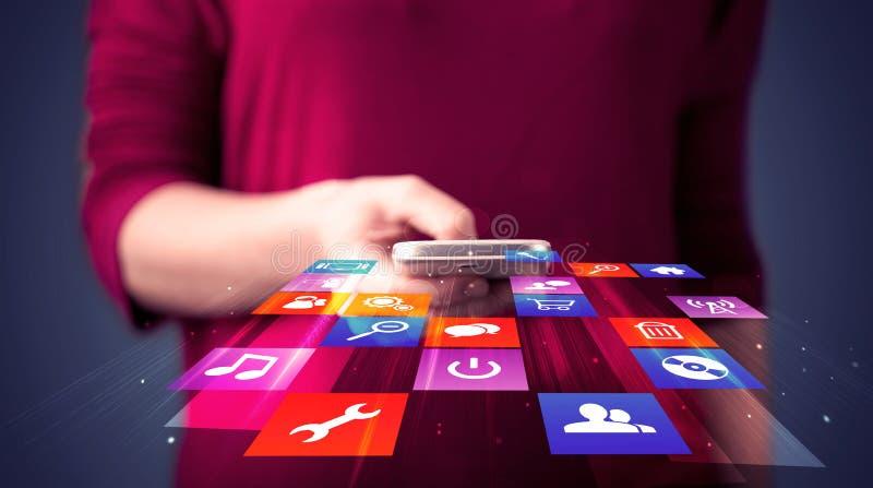 Mulher que guarda o telefone esperto com ícones coloridos da aplicação foto de stock royalty free