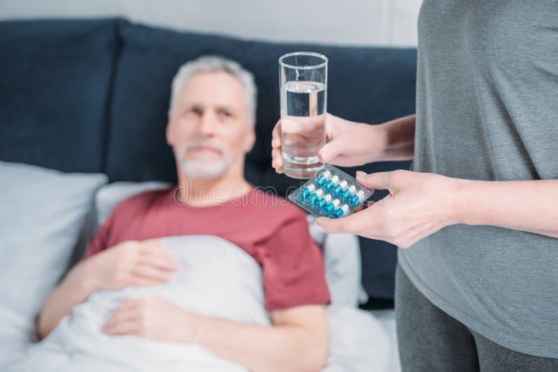 Mulher que guarda o vidro da água e das medicinas para o marido doente fotografia de stock royalty free