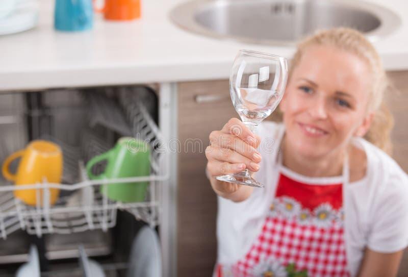 Mulher que guarda o vidro de vinho acima da máquina de lavar louça imagens de stock
