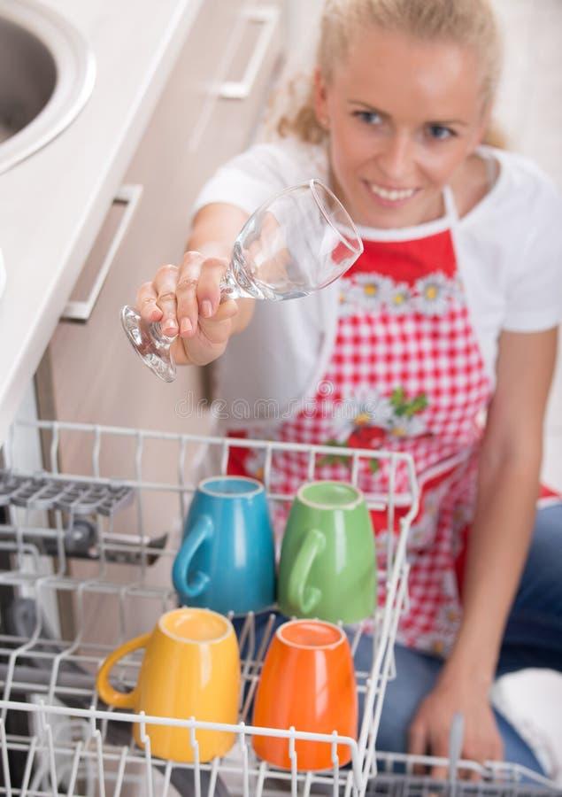 Mulher que guarda o vidro de vinho acima da máquina de lavar louça foto de stock
