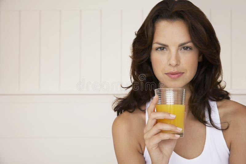 Mulher que guarda o vidro do suco de laranja imagem de stock royalty free