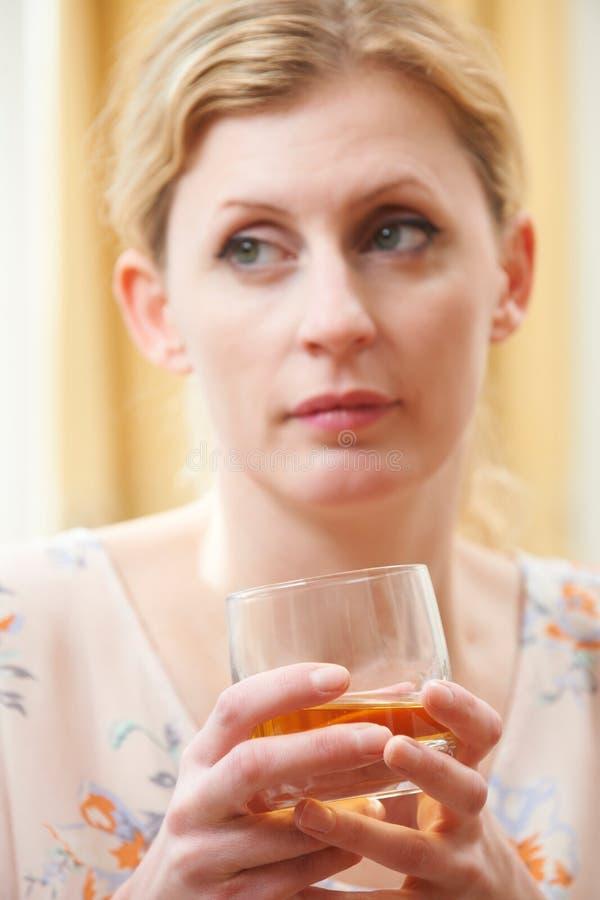 Mulher que guarda o vidro do uísque fotos de stock