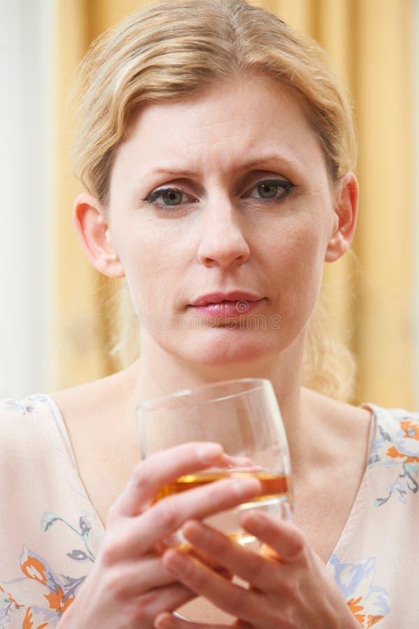Mulher que guarda o vidro do uísque fotografia de stock royalty free