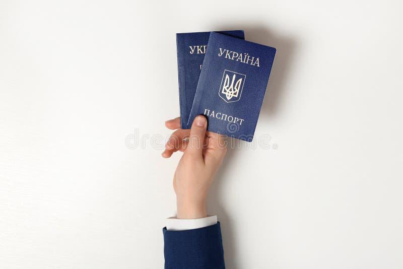 Mulher que guarda passaportes internos ucranianos no fundo claro fotografia de stock
