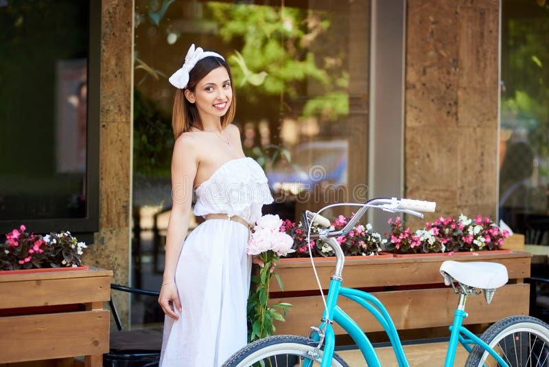 A mulher que guarda peônias aproxima a bicicleta do vintage contra o terraço do café fotografia de stock