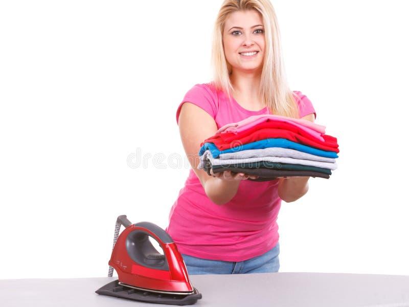 Mulher que guarda a pilha da roupa dobrada imagens de stock