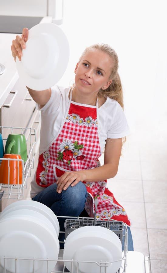 Mulher que guarda a placa acima da máquina de lavar louça fotos de stock