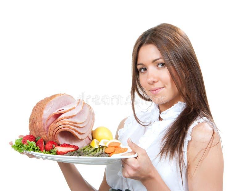 A mulher que guarda a placa nas mãos com o presunto da carne do peru decorou o lett imagens de stock royalty free