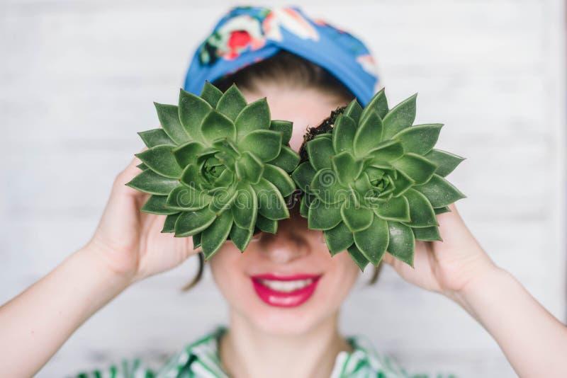 Mulher que guarda plantas carnudas perto da cara, conceito, fotos de stock