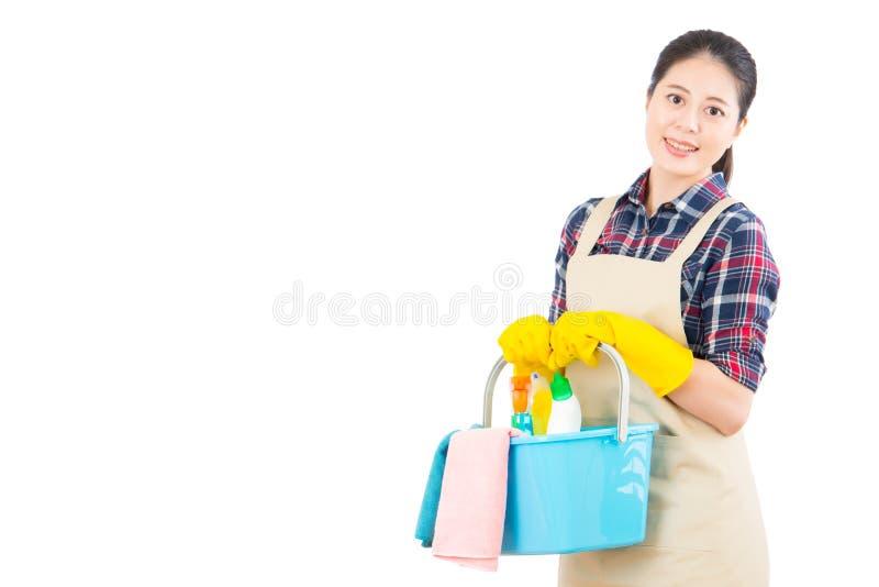 Mulher que guarda produtos de limpeza na cubeta fotografia de stock