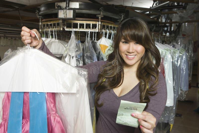 Mulher que guarda a roupa e o recibo limpados secos fotografia de stock royalty free