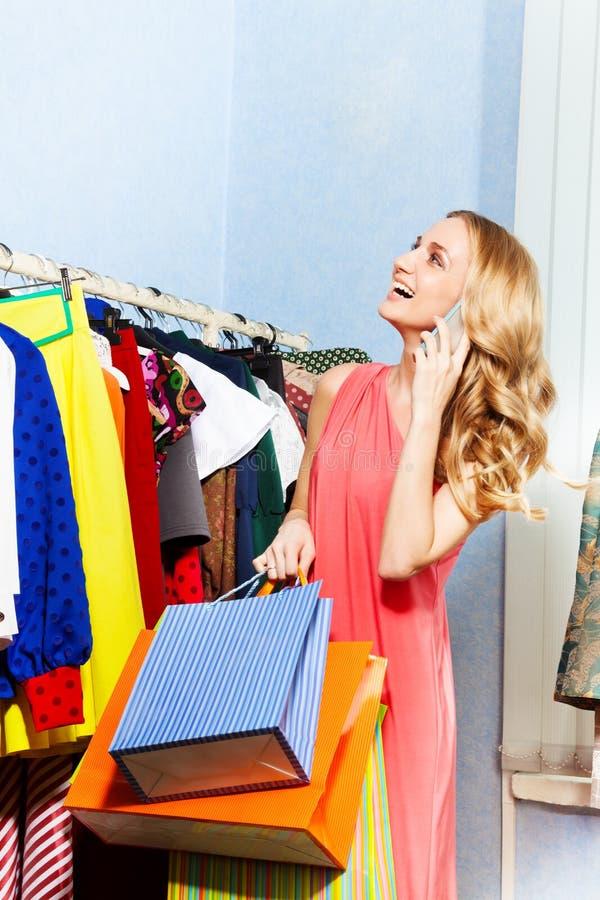 Mulher que guarda sacos de compras com telefone celular imagem de stock royalty free