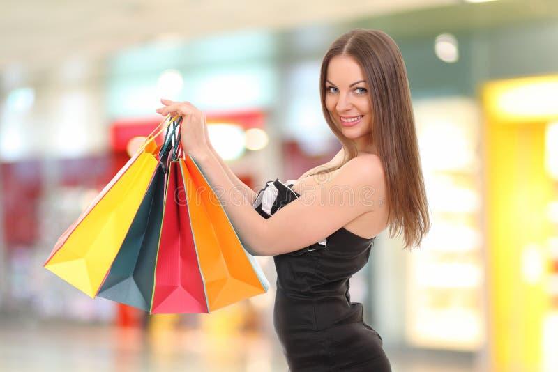 mulher que guarda sacos de compras e que sorri na câmera fotografia de stock royalty free