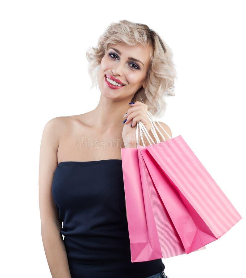 Mulher que guarda sacos de compras e que sorri no fundo branco fotografia de stock royalty free