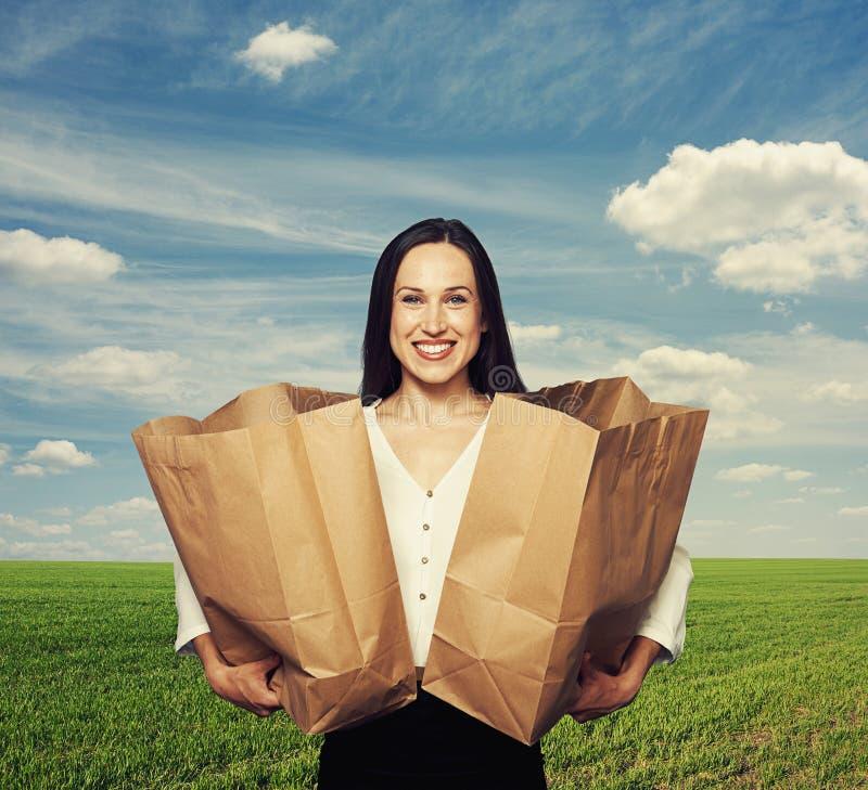 Mulher que guarda sacos de papel em exterior foto de stock