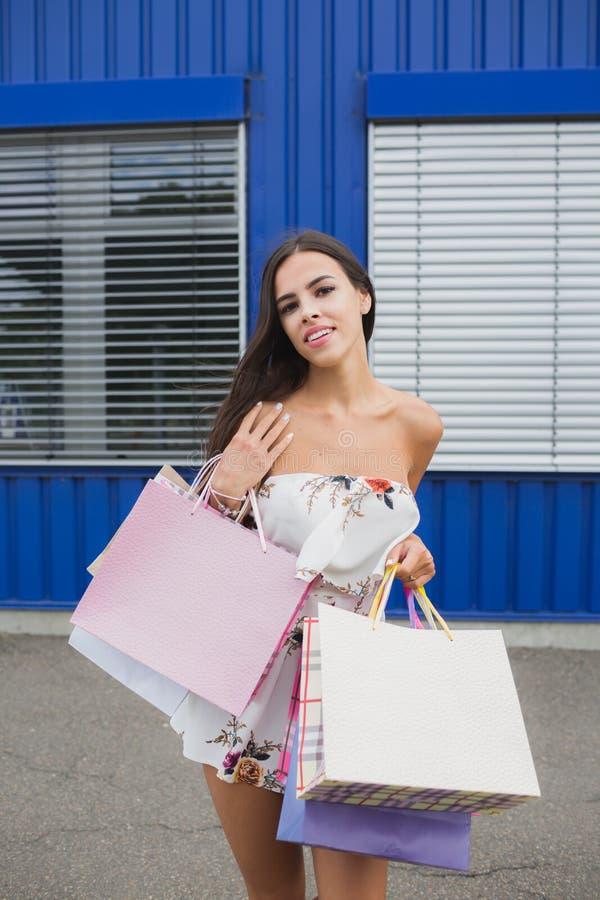 Mulher que guarda seus sacos de compras, cores diferentes em sua mão - Deixe o ` s ir comprar no conceito da alameda foto de stock