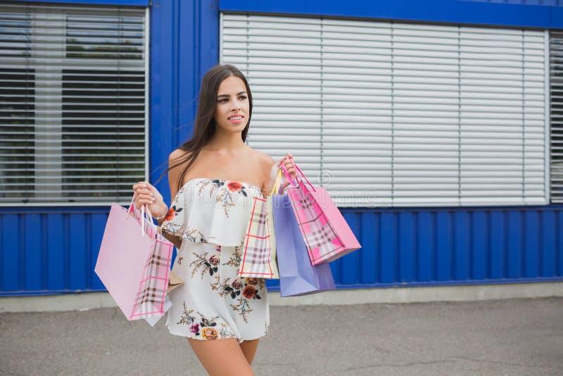 Mulher que guarda seus sacos de compras, cores diferentes em sua mão - Deixe o ` s ir comprar no conceito da alameda imagens de stock