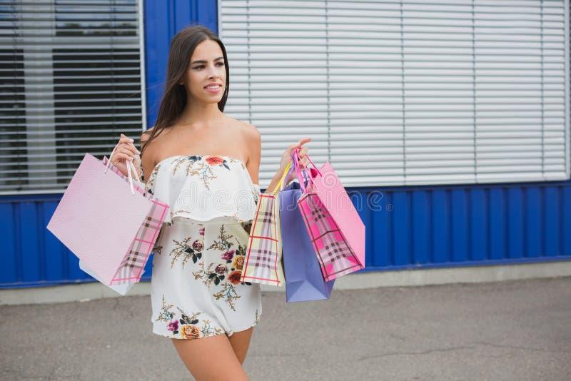 Mulher que guarda seus sacos de compras, cores diferentes em sua mão - Deixe o ` s ir comprar no conceito da alameda foto de stock royalty free
