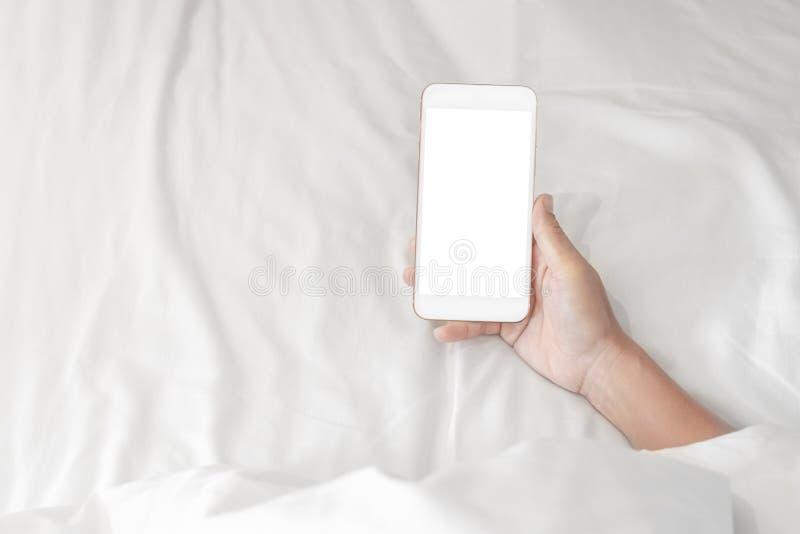 Mulher que guarda sobre seu smartphone ao dormir no fundo da cama fotos de stock royalty free