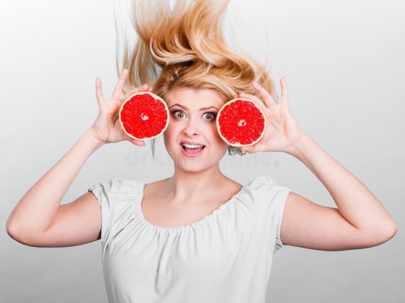Mulher que guarda a toranja vermelha que tem o cabelo windblown louco foto de stock