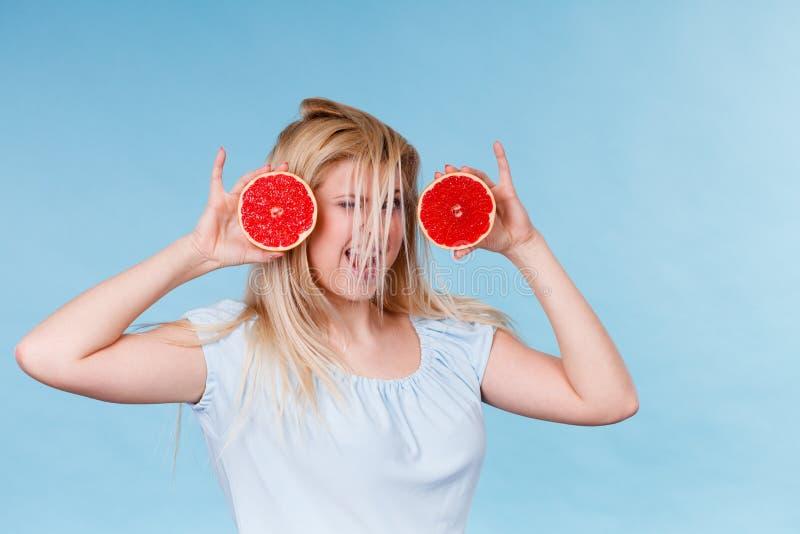 Mulher que guarda a toranja vermelha que tem o cabelo windblown louco imagens de stock royalty free