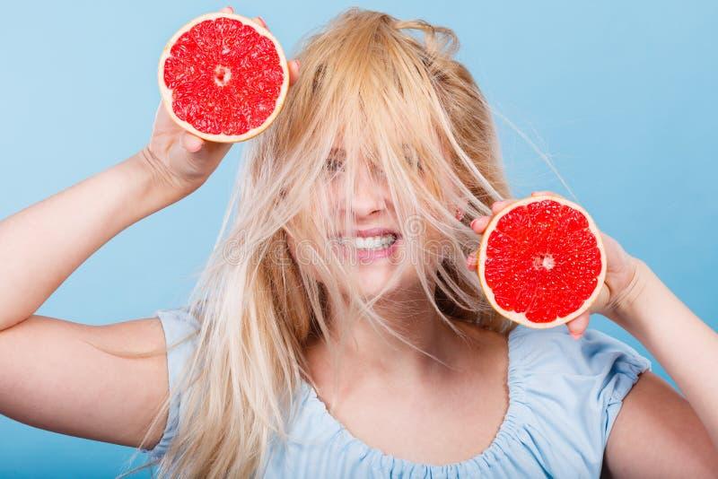 Mulher que guarda a toranja vermelha que tem o cabelo windblown louco foto de stock royalty free