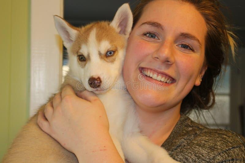 Mulher que guarda um cachorrinho ronco na casa fotografia de stock royalty free