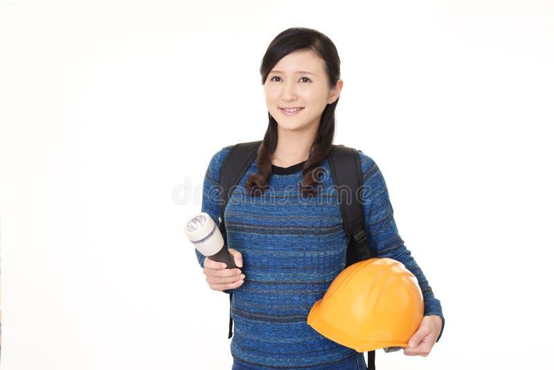 Mulher que guarda um chapéu de segurança imagem de stock royalty free