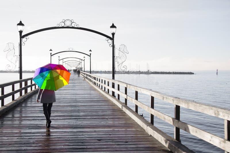 Mulher que guarda um guarda-chuva colorido arco-íris que anda em um dia chuvoso fotos de stock royalty free