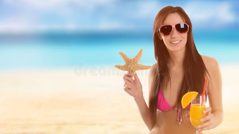 Mulher que guarda um cocktail de fruto em uma praia tropical imagens de stock royalty free