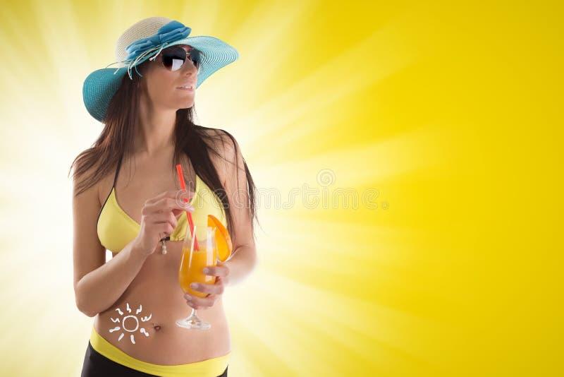 Mulher que guarda um cocktail de fruto no fundo amarelo fotos de stock royalty free