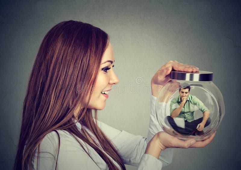 Mulher que guarda um frasco de vidro com o homem encarcerado nele imagem de stock royalty free