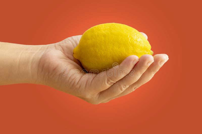 Mulher que guarda um limão nas mãos no fundo alaranjado brilhante foto de stock royalty free