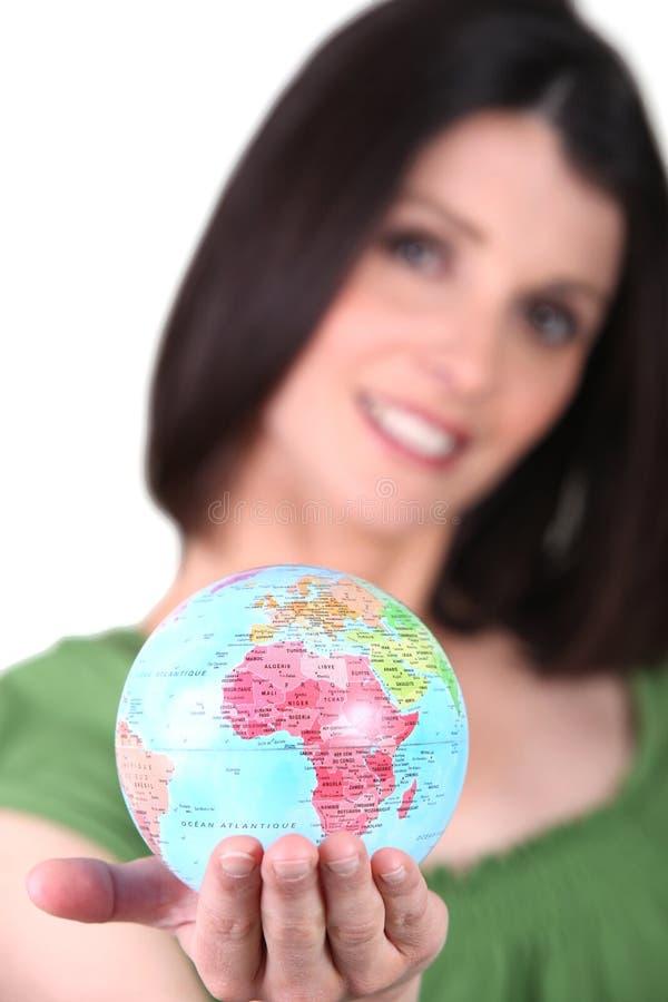 Mulher que guarda um mini-globo fotografia de stock