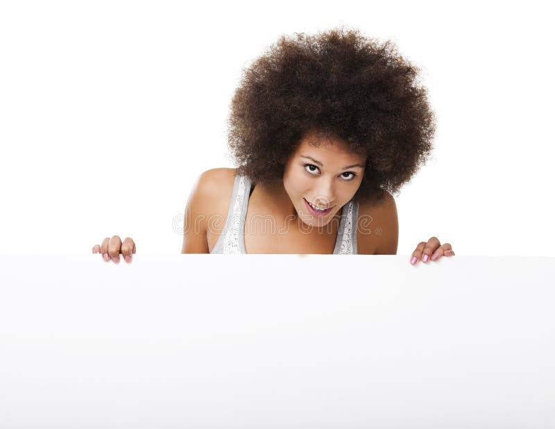 Mulher que guarda um quadro de avisos branco foto de stock