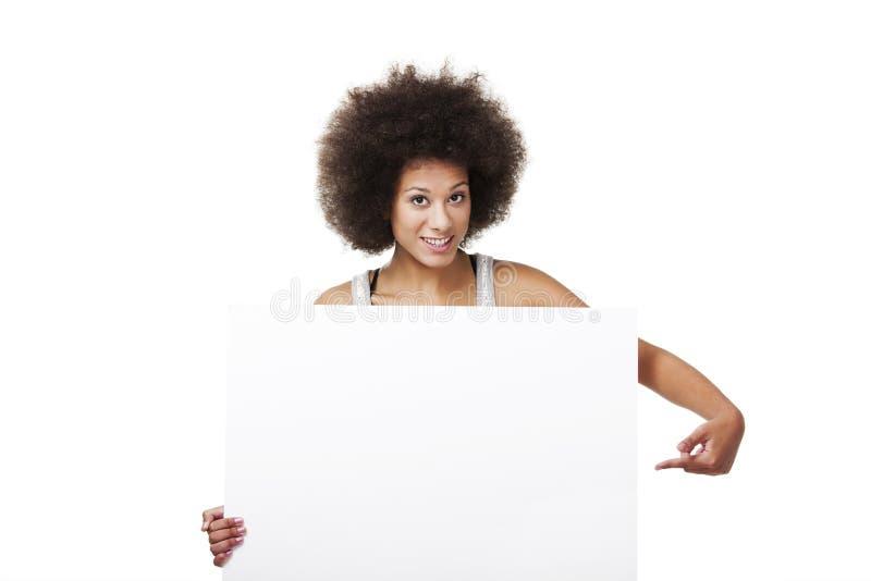 Mulher que guarda um quadro de avisos branco fotografia de stock
