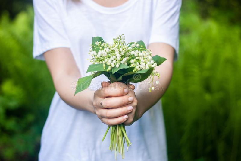 Mulher que guarda um ramalhete de lilly de flores do vale foto de stock