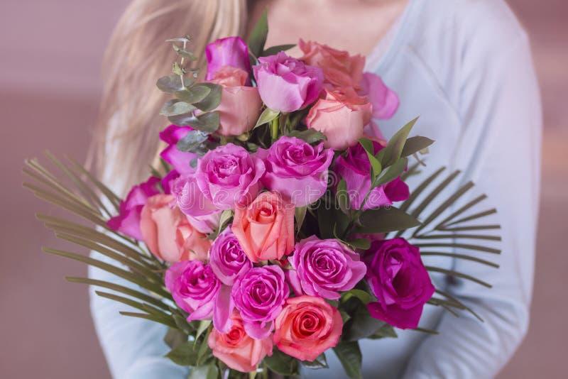 Mulher que guarda um ramalhete de rosas cor-de-rosa bonitas fotos de stock