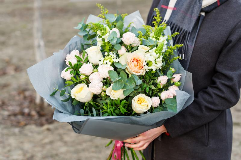 Mulher que guarda um ramalhete enorme de flores bonitas e coloridas nas m?os Nenhuma cara Foto do close up imagem de stock royalty free