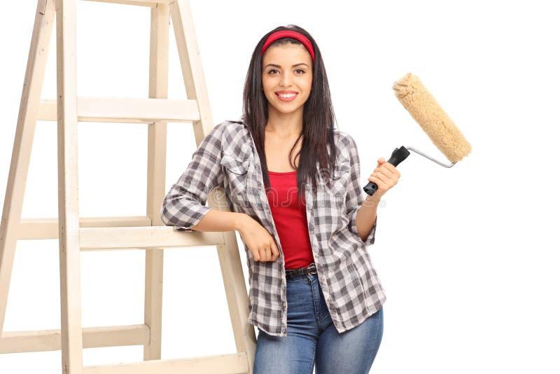 Mulher que guarda um rolo de pintura e que inclina-se em uma escada fotos de stock