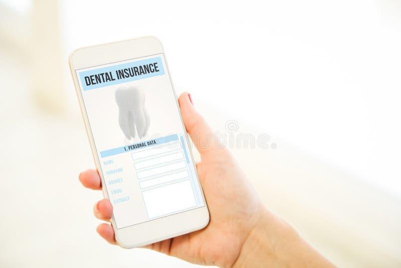 Mulher que guarda um smartphone cor-de-rosa da placa do ouro que mostra o insura dental foto de stock