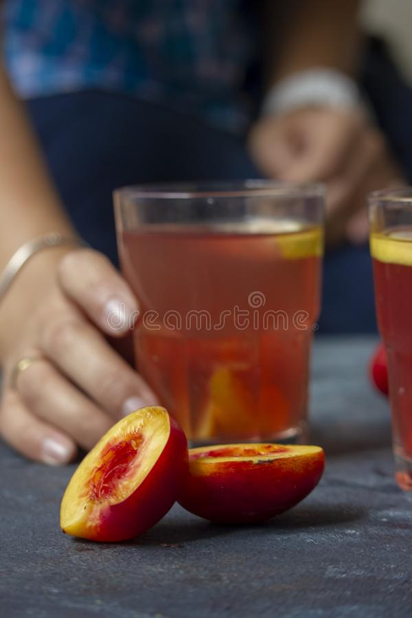 Mulher que guarda um vidro da limonada da pêssego-framboesa imagem de stock