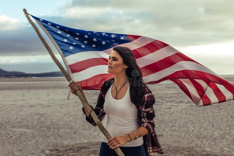 Mulher que guarda uma bandeira dos EUA na praia fotos de stock royalty free