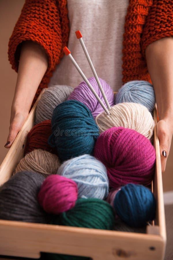 Mulher que guarda uma bola colorida do fio do witn da cesta e agulhas de confecção de malhas Foto do vertical do close-up Trabalh imagens de stock royalty free