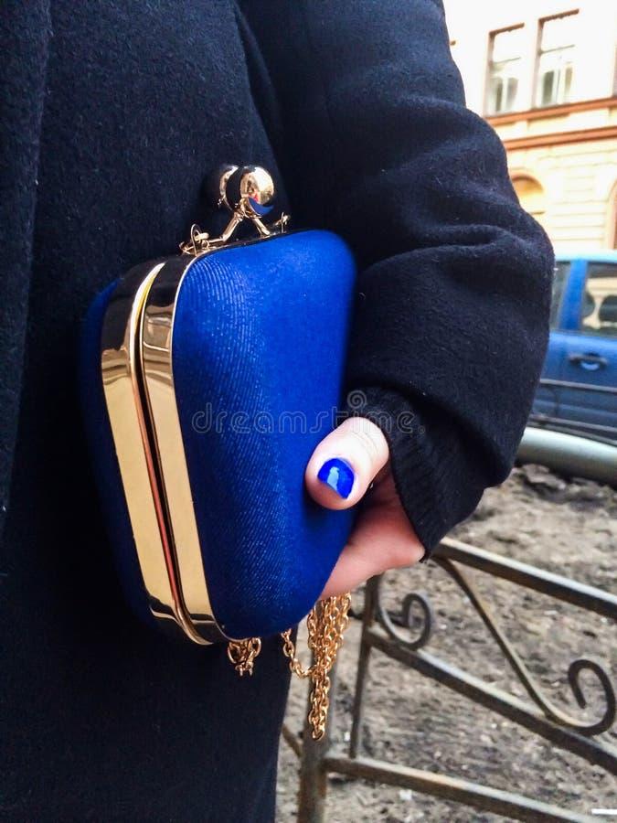 Mulher que guarda uma bolsa azul em sua mão foto de stock